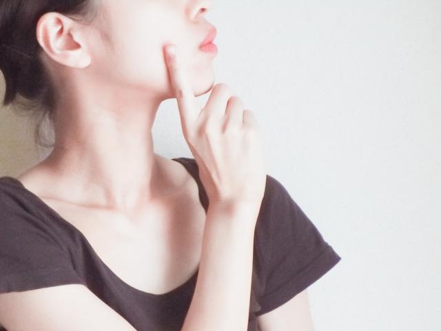 頬に人差し指を当てている女性