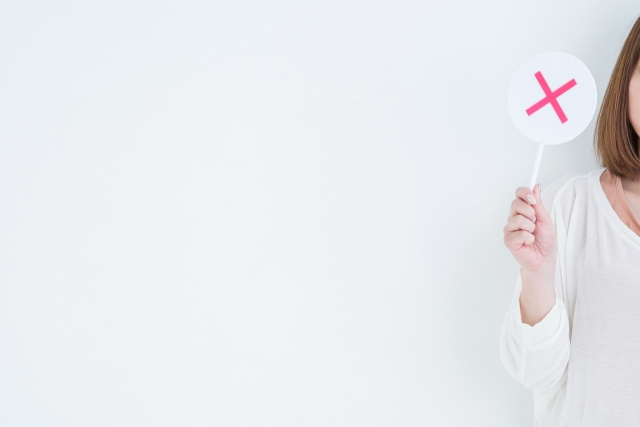 バツ印のプレートを手に持つ女性