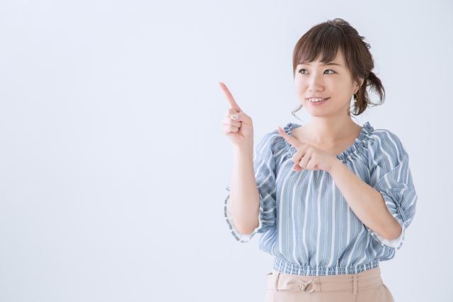 両手で指さしている女性