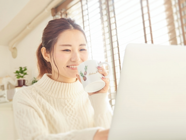 飲み物を飲みながらパソコンを見ている女性