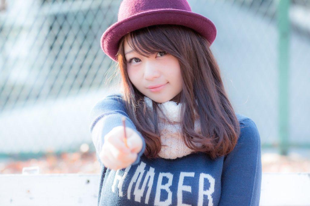 こちらに指をさしている帽子を被った女性
