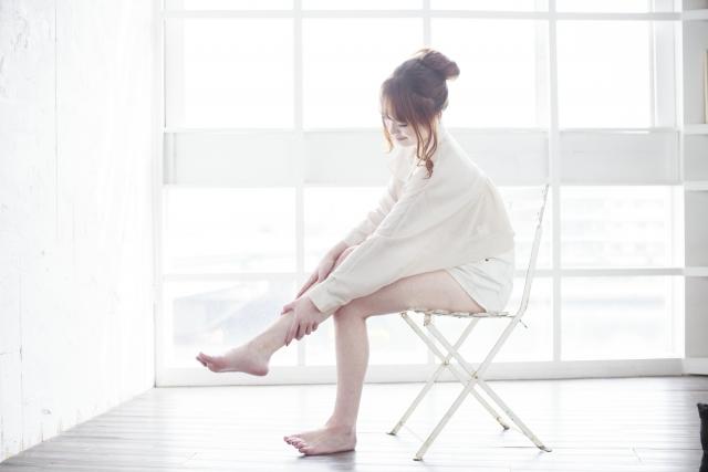 椅子に座って脚をケアしている女性の画像