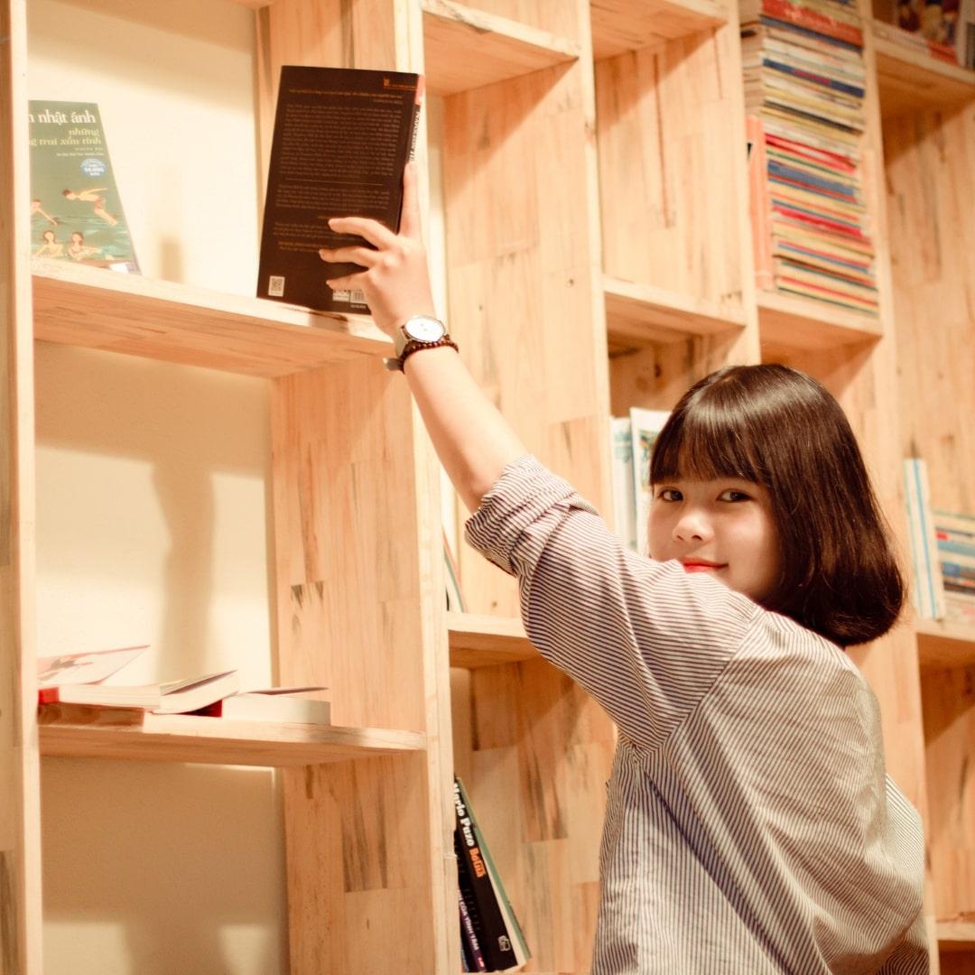 本を片付けている女性の画像