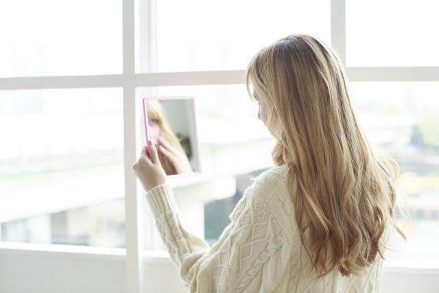 手鏡で自分の顔を見ている女性
