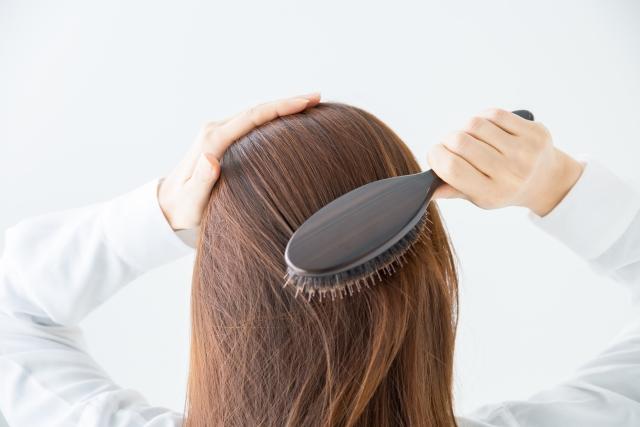 くしで髪の毛を溶かしている女性