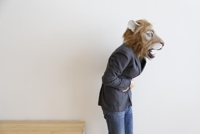 お腹を抱えているライオンの被り物を被っている女性
