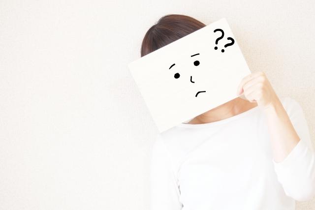 顔が書かれた紙を自分の顔に当てている女性の画像