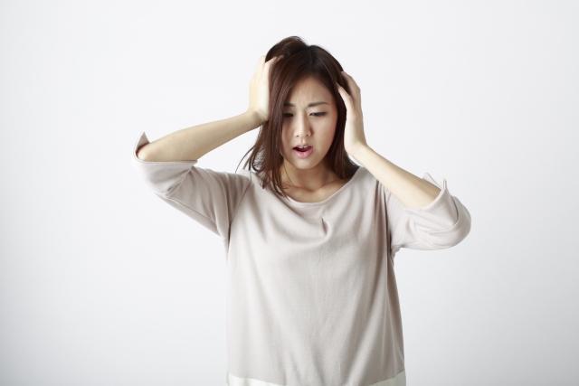 抜け毛の原因がわからないと頭を抱えている女性の画像
