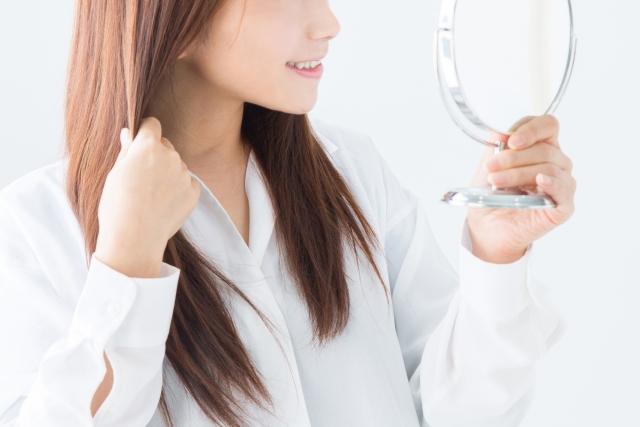 ファスティングで薄毛の改善が出来ないか悩みながら手鏡で自分の髪の毛を触っている女性の画像