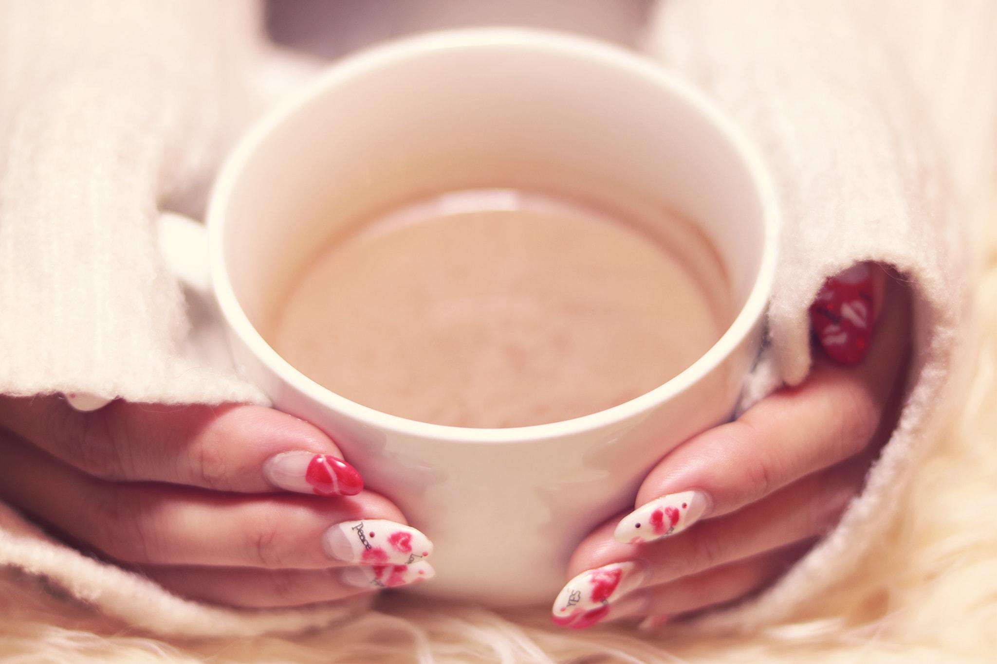 マグカップを両手で抱えている女性の画像
