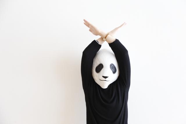 パンダの被り物をした人が両手でバツを作っている