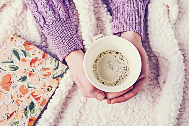 両手でコーヒーカップを持っている女性
