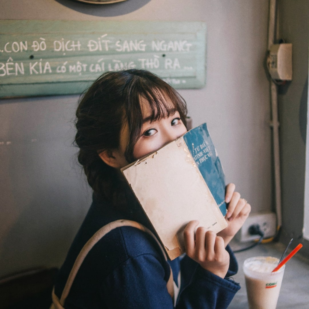 本で顔を隠している女性の画像