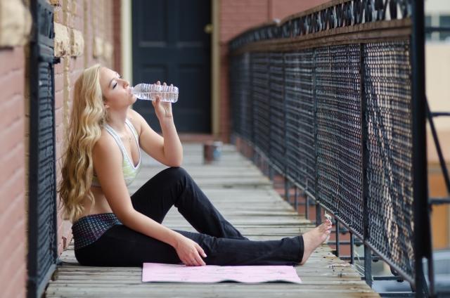 水分補給を座ってしている外人女性の画像