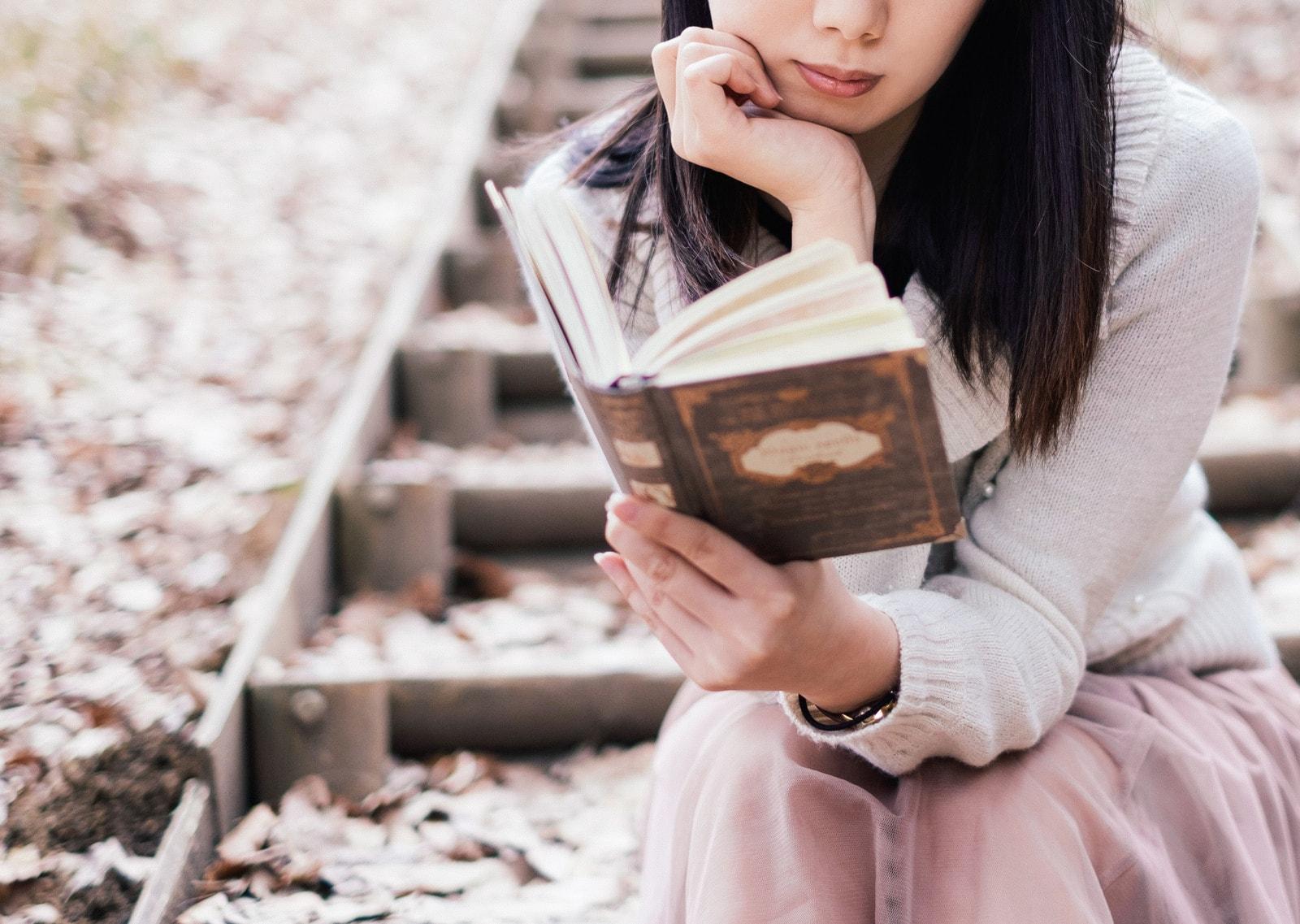 公園の階段で本を読んで座っている女性の画像