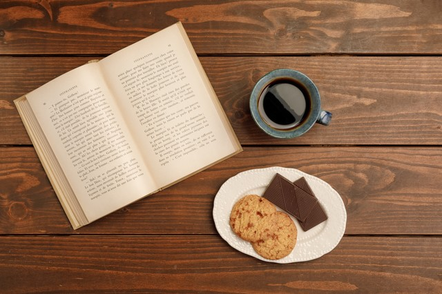本とクッキーとチョコとコーヒーが置いてあるテーブルの画像