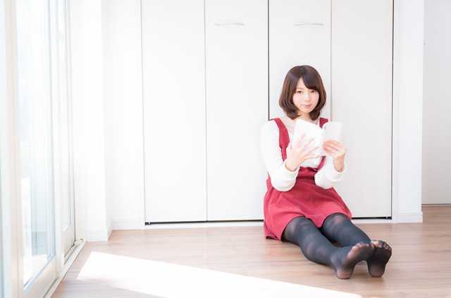 本を読んでいる赤いサロペットを着ている女性の画像