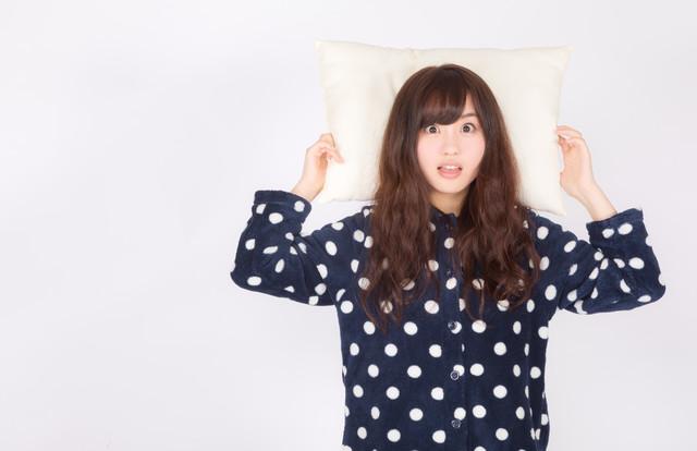 枕を抱えて驚いている女性の画像