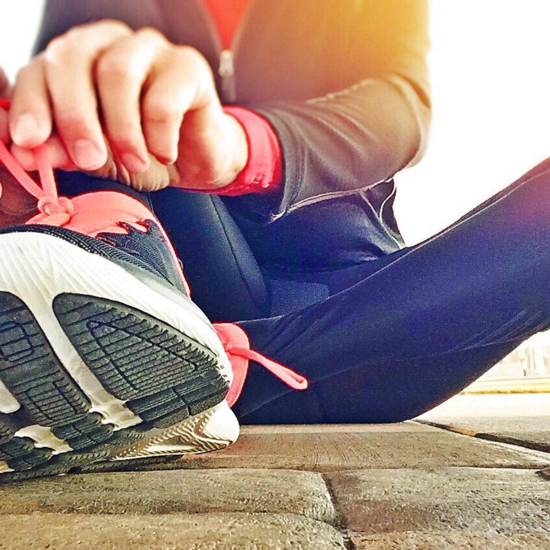 靴ひもを結んでいる女性の画像