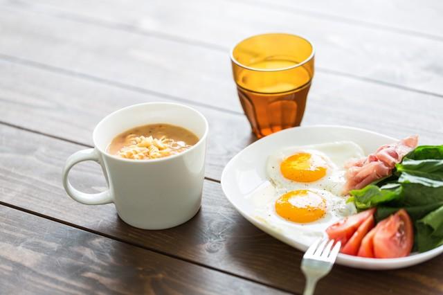 目玉焼きとサラダとスープの食事の画像