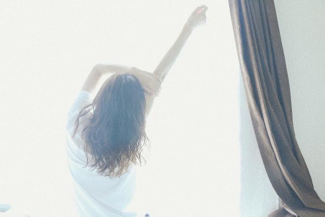 カーテン越しに背伸びをしている女性の画像