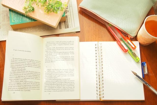 テーブルの上にノートと鉛筆とお茶の画像