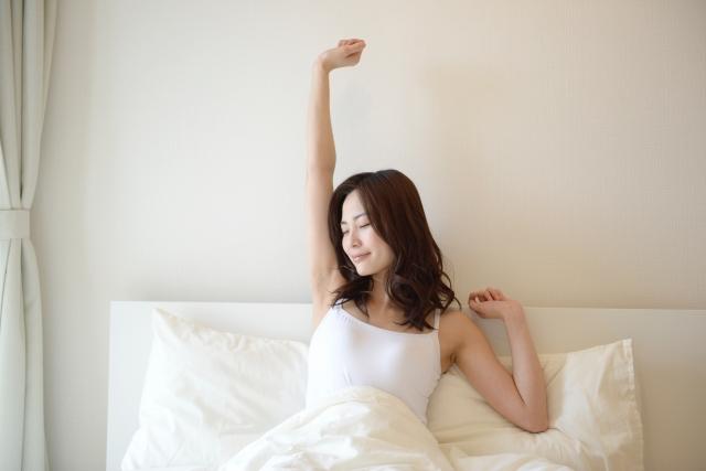 ベッドで起きたばかりの女性の画像