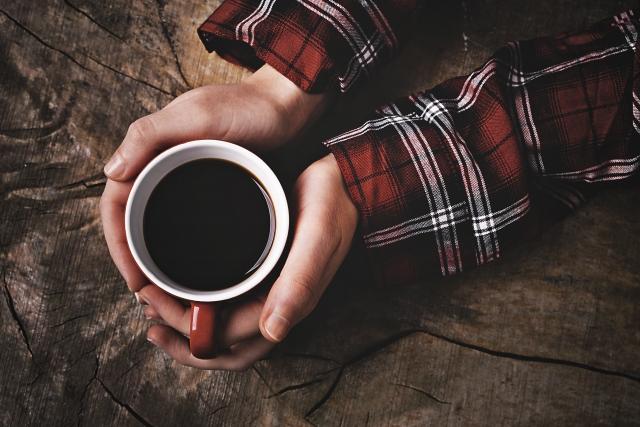 コーヒーを両手で支えている手の画像