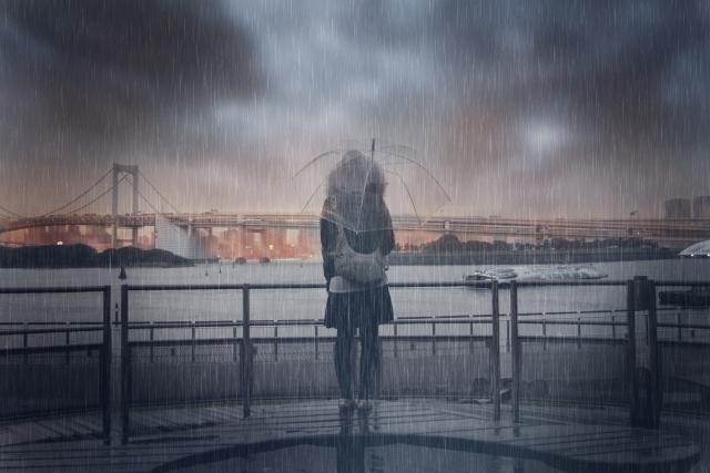 雨の中傘をさして立っている女性の画像