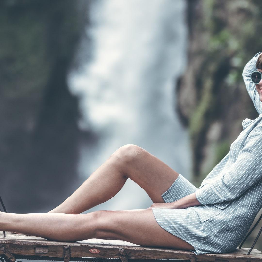 滝の近くでポーズをとっている外人女性の画像