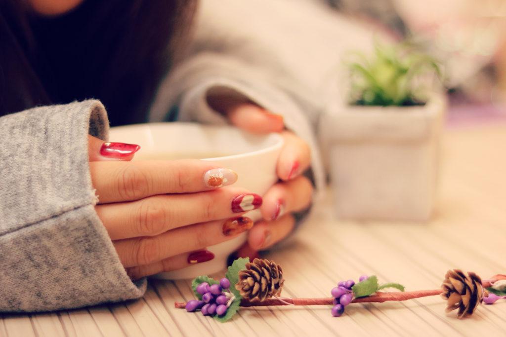 酵素ドリンクの入ったマグカップを両手で支えている女性の手の画像