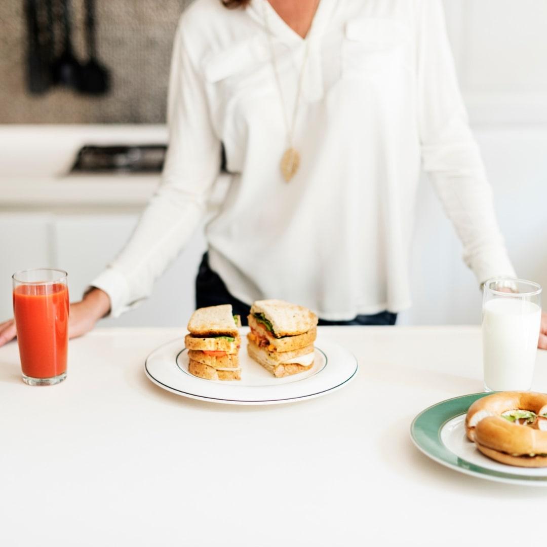 キッチンでサンドイッチと女性が立っている画像
