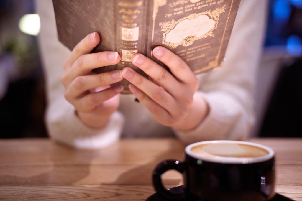 本を読みながらコーヒーを飲む女性の画像