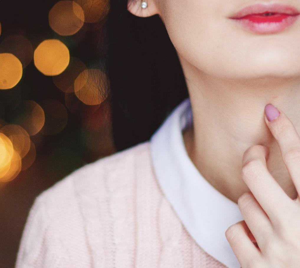 首元を指で触れている女性の画像