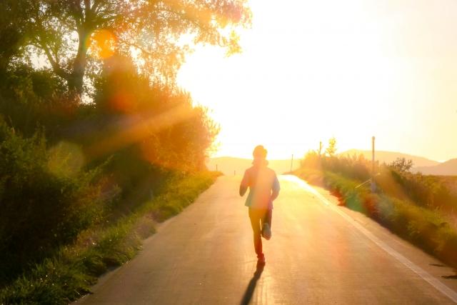 夕日に向かって走っている人の画像