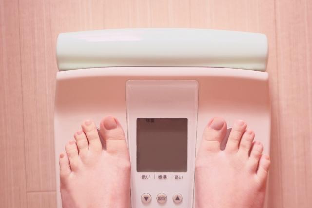 体重計に乗っている脚の画像