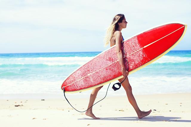 サーフボードを持っている女性の画像
