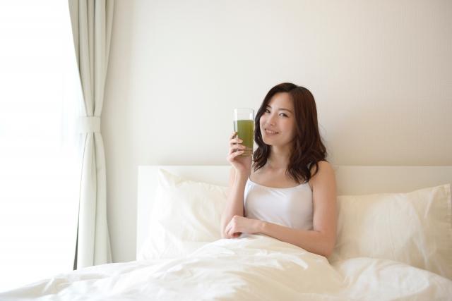 ベッドでスムージーを飲んでいる女性の画像