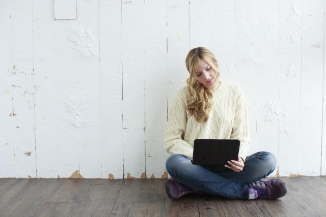 パソコンを見てTwitterのフォロワーが増えないと落ち込んでいる女性の画像