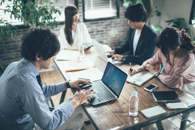 Twitterを研究しているパソコンを開いている4人の男女の画像