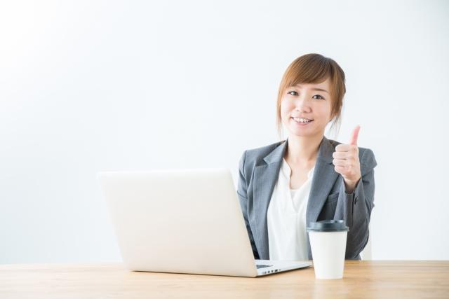 グッドの手をしてパソコンを開いている女性の画像