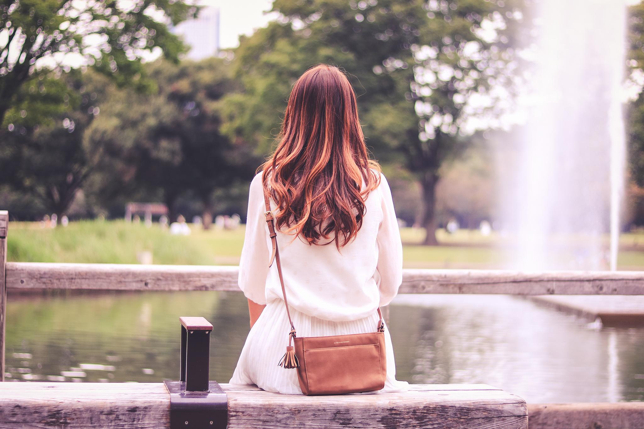 自分の価値が低いと落ち込んで噴水前に座っている女性の画像