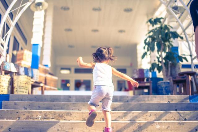 嫌な生活から抜け出そうと階段をかけあがる子供の画像
