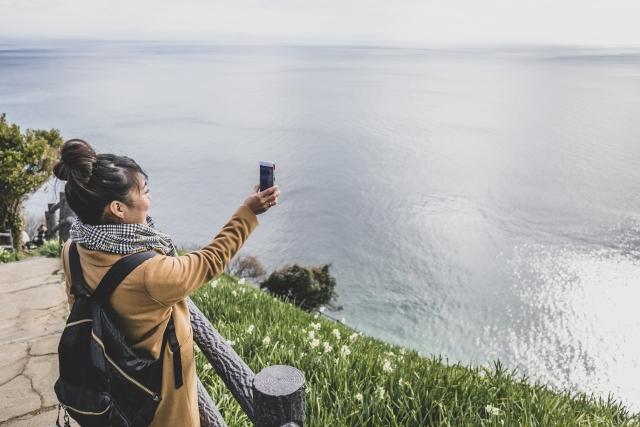 悩み解消するために旅行して海を写真撮っている女性の画像