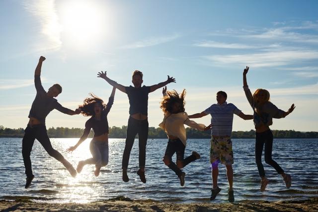 海の砂浜で楽しくジャンプして遊んでいる6人の大人の画像