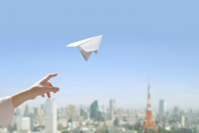 紙飛行機を空に向かって飛ばしている画像