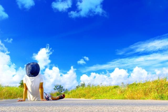 空を見上げて道路に座っている男性の画像