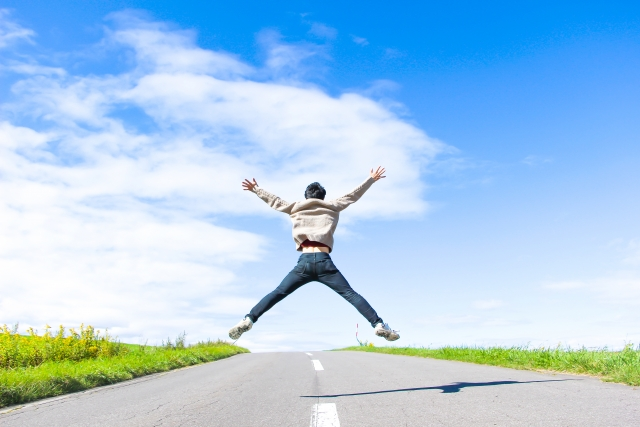 両手広げて道路の真ん中でジャンプしている男性の画像