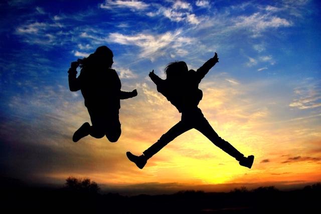 夕焼けの中ジャンプしているカップルの画像