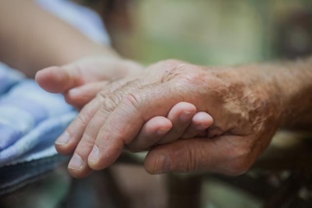 老人へ感謝の気持ちを込めて手を支えている画像